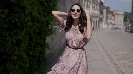 caminhada : Fashion hipster style girl walks through the summer city streets in floral pattern color dress and dark sunglasses Vídeos