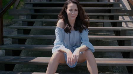 merdiven : Adorable brunette woman sitting on stairs in outdoor. Wearing summer blue dress and looking at camera. Stok Video