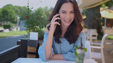 cold drinks : Pretty brunette woman sitting in outdoor restaurant and talking her mobile phone. Summer time in the city. Stock Footage