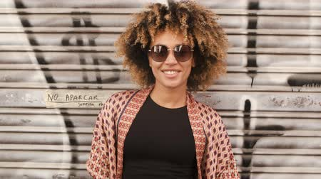 граффити : Portrait of contemporary young ethnic woman with Afro hairstyle wearing sunglasses and smiling happily at camera standing against street wall with graffiti