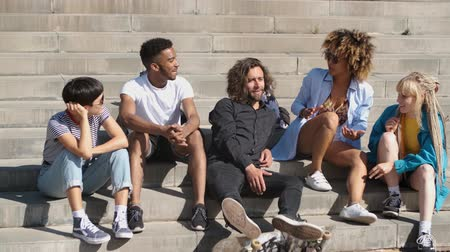 passo : Cool modern multiethnic men and women in casual clothes sitting on concrete steps and spending time in summertime chatting happily