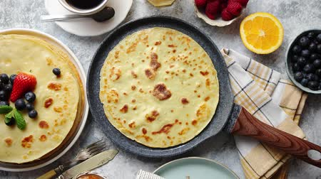 блин : Delicious pancakes on stone frying pan. Placed on table with various ingredients on side. With fresh fruits, black coffee cup. Flat lay. View from above.