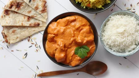 tikka : Fresh and tasty Butter Chicken served in ceramic bowl. Indian mild traditional dish. With rice and naan bread on sides. Close up. Flat lay.