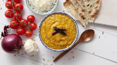 kari : Indian popular food Dal fry or traditional Dal Tadka Curry served in ceramic bowl with rice and naan bread. Placed on white wooden table. Closeup view over.