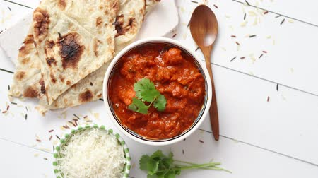 tikka : Fresh and tasty Chicken tikka masala served in ceramic bowl. Indian spicy curry dish. With rice and naan bread on sides. Close up. Flat lay.