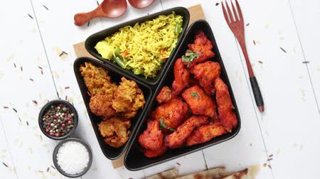 tandoori : Spicy indian fried chicken served with curry vegetable rice, onion bhajia, naan bread. Placed on white wooden table.