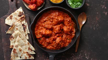 kari : Traditional Indian chicken tikka masala spicy curry meat food in cast iron pan served with naan bread and spices. Flat lay. Top view.