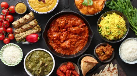 tikka : Assortment of various kinds of Indian cousine on dark rusty table. Chicken Tikka Masala, Butter, Nilgiri, Daal Tarka. Served with fried rice, naan bread and spices.