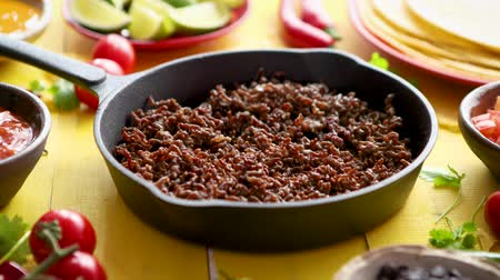 çili : Various fresh and tasty ingredients for chilli con carne. With meat on iron pan, tortillas, vegetables, cheese, bean. Placed on wooden yellow table