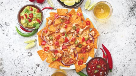 chicken recipes : A plate of delicious tortilla nachos with melted cheese sauce, grilled chicken, jalapeno peppers, red onion, tomato, guacamole dip and spicy salsa. With cold sparkling beer.