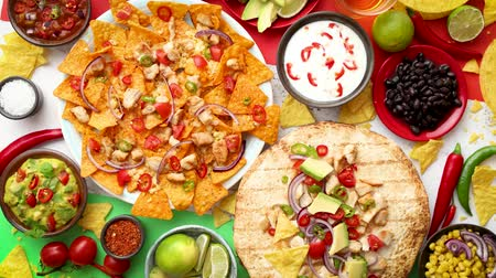 chilli sauce : An overhead photo of an assortment of many different Mexican foods, including tacos, guacamole, nachos with grilled chicken, tortillas, salsas and others Stock Footage
