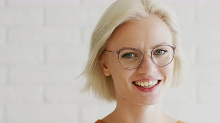 dişlek : Attractive young female with short blond hair and cheerful toothy smile wearing stylish glasses and looking at camera while standing on background of white brick wall.