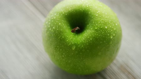 食料品 : Closeup shot of green wet apple placed on light wooden background