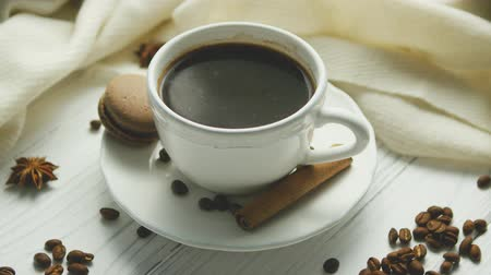 elegant dessert : White elegant cup on saucer filled with black coffee and composed on white wooden table with spices