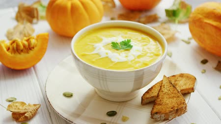 pumpkin pieces : Yellow creamy pumpkin soup in bowl with pieces of bread surrounded by pumpkins on wooden table Stock Footage