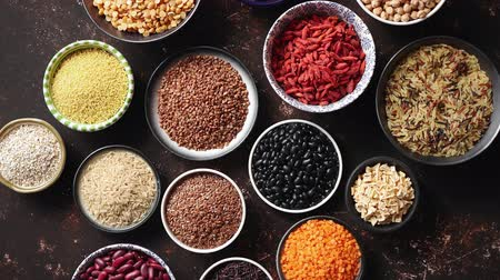 curcuma : Various superfoods in smal bowls on dark rusty background. Superfood as rice, lentil, beans, peas, goji, flaxseed, buckwheat, couscous, chickpeas Top view Flat lay