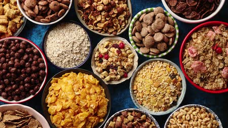 oat flakes : Assortment of various kinds cereals placed in ceramic bowls with cornflakes, granola, cereals and oatmeal. Flat lay, top view on blue rusty table with copy space in the middle Stock Footage