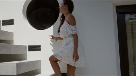 stair : Side view of pretty young brunette wearing white dress with open shoulders climbing stairs of house with white walls