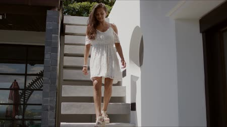 saçlı : From below of beautiful young long haired female wearing white dress with open shoulders walking down stairs in patio of house with white walls