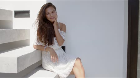 lépcsőfok : Side view of cheerful laughing long haired female in beautiful white lace dress with bare shoulders sitting on stairs. next to white wall and looking at camera