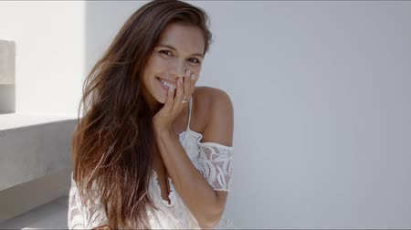 saçlı : Charming romantic long haired brunette in white lace dress with open shoulders sitting on stairs and looking at camera with happy embarrassed smile