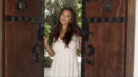 saçlı : Happy confident young long haired brunette wearing white low cut dress opening old fashioned wooden doors with metal handles