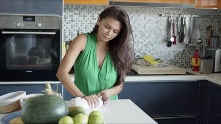 ustensile : Beautiful relaxed brunette standing at counter with shiny fruit and concentrated on kneading dough while making pastries in kitchen at home