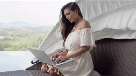 тачпад : Attractive pensive adult lady in white dress focusing on screen and interacting with laptop while sitting on sofa. against amazing view of forested countryside on terrace Стоковые видеозаписи