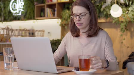 clear the table : Smart businesswoman in glasses typing on laptop and drinking tea at table in light cafe