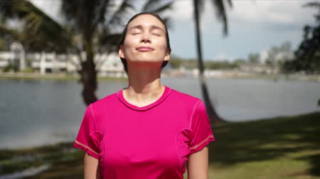 à beira do lago : Happy joyful female wearing pink sport shirt standing on tropical lakeside on sunny summer day