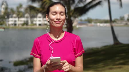 à beira do lago : Young female in pink shirt choosing playlist on smartphone while listening to music with earphones during morning walking on tropical lakeside