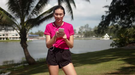à beira do lago : Young cheerful sportive female wearing shirt and shorts using smartphone and earphones and enjoying music while walking on tropical lakeside Stock Footage