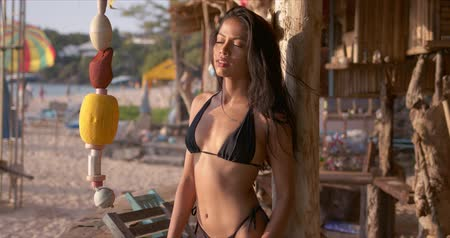 dark island : Delightful slim long haired brunette in sexy black bikini leaning back against wooden pole of beach bar in tropical seaside in Phuket Thailand