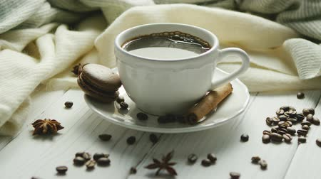 White elegant cup on saucer filled with black coffee and composed on white wooden table with spices