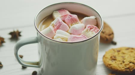 гарнир : White mug filled with sweet cacao and marshmallows served on table with cookies and spices
