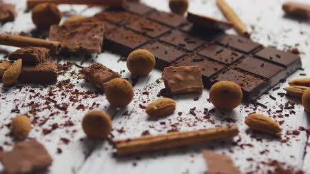 Closeup of arranged mess of black chocolate bar with milk chocolate pieces and spices on wooden table