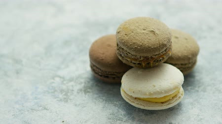 macarons : Closeup of white and chocolate macarons with different fillings composed in small heap on marble surface Stock Footage