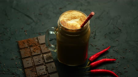 From above view of dark foamy drink in glass mug with chili and bar of chocolate placed near on gray background Stock mozgókép