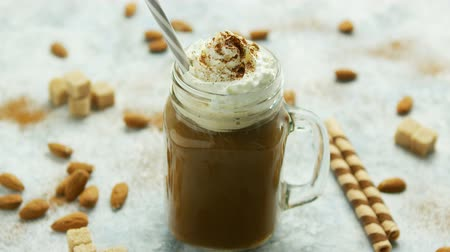 Glass jar with sweet caramel drink garnished with whipped cream and served with straw on table among nuts