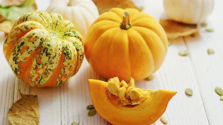 From above view of orange ripe pumpkins laid on wooden background and decorated with withered leaves