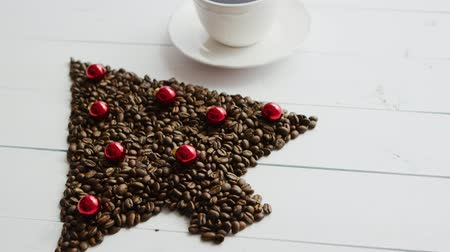 From above view of brown coffee beans laid in shape of Christmas tree decorated with little red balls with cup placed near on white background