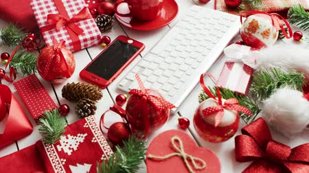 Various symbols of Christmas lying on table around cup of aromatic hot drink and modern devices