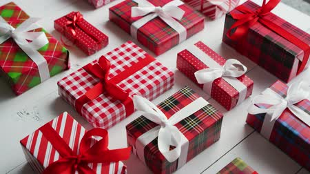 Side view of wrapped Christmas presents laid on the white wooden table