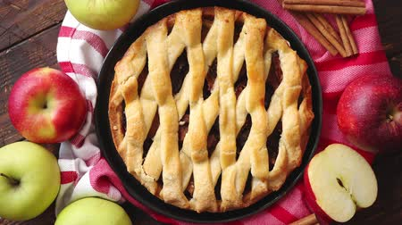 cuisine dark : Homemade pastry apple pie with bakery products on dark rusty wooden kitchen table red and green apples and cinnamon. Traditional american dessert. Flat lay food background. Top view Stock Footage