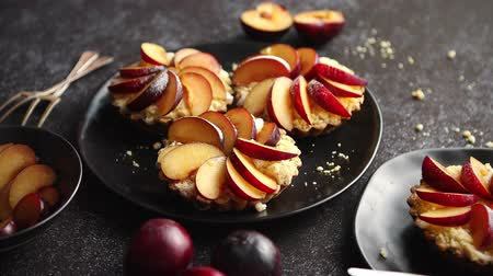 tartlet : Delicious homemade mini tarts with fresh sliced plum fruit. Sprinkled with icing sugar. Placed on black ceramic plates with fresh pieces of plums on sides. Dark rusty background from top. Stock Footage