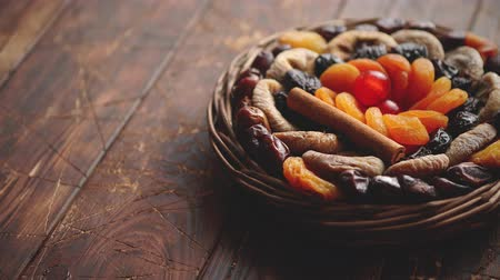 изюм : Mix of dried fruits in a small wicker basket on wooden table. Assortment contais apricots, plums, figs, dates, cherries, peaches. Above view with copy space.