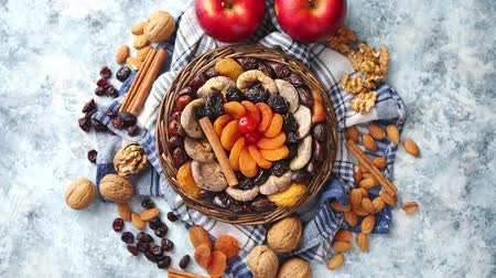jodendom : Composition of dried fruits and nuts in small wicker bowl placed on a stone table. Assortment contais almonds, walnuts, apricots, plums, figs, dates, cherries, peaches. Above view with copy space.