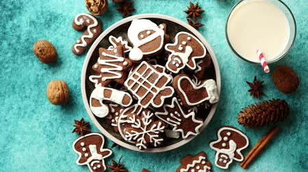 Sweet Christmas composition. Assortment of gingerbread cookies on a plate. Glass of milk, vanilla sticks, anise, pine, walnut. Top view. On blue background.