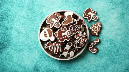 Rustical plate filled with delicous, varous Christmas shaped gingerbread cookies. Top view. Placed on blue rustic background.