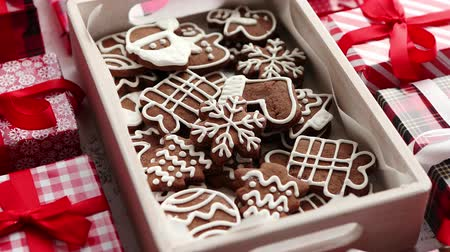 kardan adam : Delicious fresh Christmas decorated gingerbread cookies placed in wooden crate. Wrapped gifts on sides. White rusty background. Top view. Stok Video